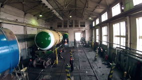 Workers repairing the tank car in hangar stock footage