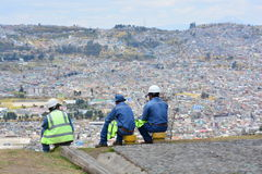 Workers resting in Quito, Ecuador. Construction workers resting after a long day of work over a mountain, with the city of Quito as background royalty free stock image
