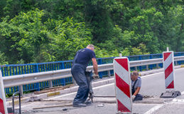 Workers restore the road near the monastery of Moraca. Stock Image