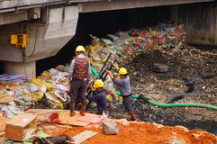 Workers in the river construction, pry an iron shelf Stock Image