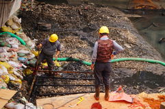 Workers in the river construction, pry an iron shelf Royalty Free Stock Photo