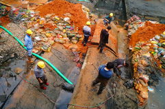 The workers are on the river drainage pipeline maintenance. In Shenzhen, china Stock Photo