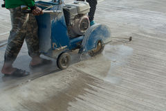 Workers on a road construction use a blade cuting floor Royalty Free Stock Images
