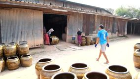 Workers rolling Dragon design jars out of kiln in pottery industry at Ratchaburi province. stock video footage