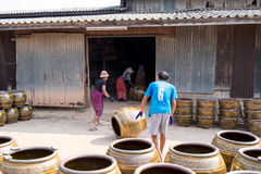 Workers rolling lots of Dragon design pots and flower pots from stove. March 5, 2017 - Ratchaburi, Thailand: workers rolling lots of Dragon design pots and Royalty Free Stock Photos