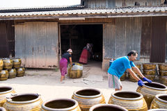Workers rolling lots of Dragon design pots and flower pots from stove. March 5, 2017 - Ratchaburi, Thailand: workers rolling lots of Dragon design pots and Stock Image