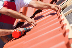 Workers on a roof with electric drill installing red metal tile on wooden house. Stock Images