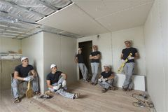 Workers in room with aluminum foil on walls and ceiling and drywall. Reconstruction and insulation. stock image