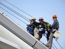Workers on safety harnesses