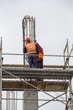 Workers on scaffold platform tied rebar and steel bars Stock Images