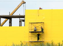 Workers on scallolding. On yellow wall background Royalty Free Stock Photos