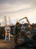 Workers at scrap metal junkyard. Caucasian engineer standing at scrap metal recycling site, inspecting work Royalty Free Stock Photos