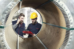 Workers seen through a steel sheet metal roll Royalty Free Stock Images