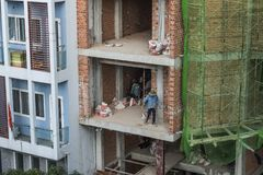 Workers are setting the electricty up in the wall of a bricks building in Vietnam royalty free stock photo
