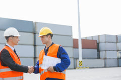 Workers shaking hands in shipping yard Royalty Free Stock Images