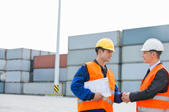 Workers shaking hands in shipping yard Stock Photos