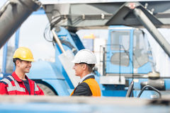 Workers shaking hands in shipping yard Stock Photo