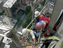 Workers on side of skycraper Royalty Free Stock Photos