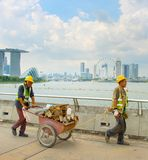 Workers in Singapore Marina Bay. SINGAPORE - JAN 15, 2017: Two workers pushing a cart in front of Singapore Downtown. Construction industry is expected to pull Stock Photo