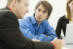 Workers sit and talk. Near a desk Royalty Free Stock Photography