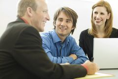 Workers sit and talk. Near a desk Stock Image