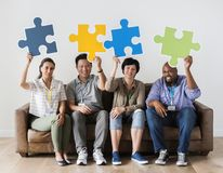 Workers sitting and holding puzzle icons Stock Images