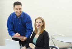 Workers smile near desk. Two workers smile as the work near a desk Stock Photo