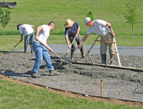 Workers smoothing concrete. Using rakes and a float Royalty Free Stock Photo