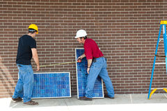 Workers with Solar Panels Royalty Free Stock Photo