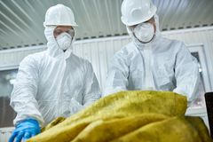 Workers Sorting Plastic on Recycling Plant. Low angle portrait of two workers wearing biohazard suits working at waste processing plant sorting recyclable royalty free stock photography