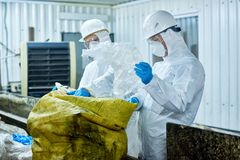 Workers sorting plastic on trash recycling plant. Portrait of two workers wearing biohazard suits working at waste processing plant sorting recyclable plastic on royalty free stock photography