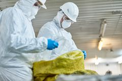 Workers Sorting Plastic on Trash Recycling Plant. Side view portrait of two workers  wearing biohazard suits working at waste processing plant sorting recyclable royalty free stock photography