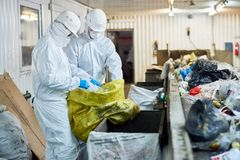 Workers sorting recyclable materials at waste processing plant. Side view portrait of two workers wearing biohazard suits sorting recyclable plastic and royalty free stock photography
