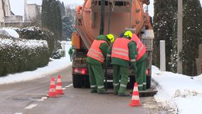 Workers with special equipment unstop sewage drain system on street