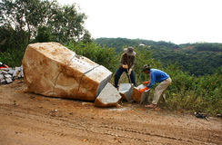 Workers split large rock for road-works stock photos