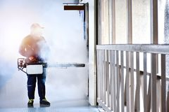 Workers are spraying get rid of mosquitoes. On the building, Put on a gas mask and protective suit Stock Image