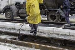 Workers sprays bitumen emulsion onto the road 2 Stock Photo