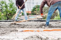 Workers spreading concrete over the slab. Of a house under construction. Structural parts of a house, building background. Steel beams and electrical mains royalty free stock photography