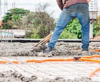 Workers spreading concrete over the slab. Of a house under construction. Structural parts of a house, building background. Steel beams and electrical mains stock photography