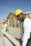 Workers Stacking Boards At Construction Site Stock Photos