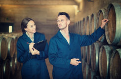 Workers standing with clipboard and labeling woods in cellar. Portrait of men and women winery workers standing with clipboard and labeling woods in cellar Stock Photo