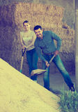 Workers standing with metallic spades. Happy mature men and smiling young women standing with metallic spades in hangar with sand pile Royalty Free Stock Photography