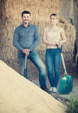 Workers standing with metallic spades. Man and young women standing with metallic spades in hangar with sand pile Royalty Free Stock Images
