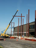 Workers and Steel Beams. Workers placing steel beams in front of building Royalty Free Stock Photos