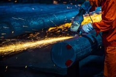 The workers in the steel mill are burnishing the steel. Sparks fly royalty free stock image