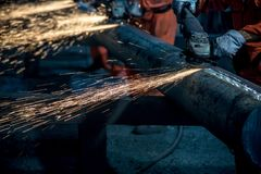 The workers in the steel mill are burnishing the steel. Sparks fly stock photos