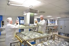 Workers in sterile protective clothing for quality control of in Royalty Free Stock Photo