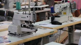 Workers and stitching machines at clothing factory stock video footage