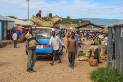 Workers at the street market unload a car with goods. Mpulungu, Zambia - March 23, 2015: workers at the street market unload a car with goods royalty free stock image