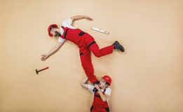 Workers in studio. Construction workers have an accident. Funny studio poses Royalty Free Stock Photography